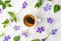 Cup of coffee and purple flowers on bed sheets Royalty Free Stock Photos
