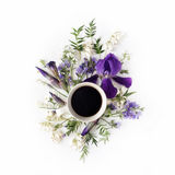 Cup of coffee with purple iris and lily of the valley flowers Stock Photo