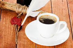 Cup of coffee with a quill pen and ink scroll Stock Photography
