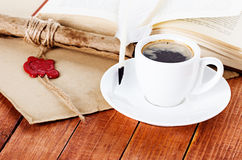 Cup of coffee with a quill pen and ink scroll Royalty Free Stock Photos