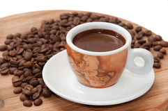 A cup of coffee with raw coffee beans Stock Photos