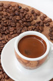 A cup of coffee with raw coffee beans Stock Photography