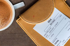Cup of coffee and receipt bill in folder  payment Royalty Free Stock Photography