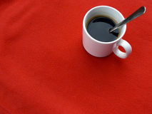 Cup of coffee on red. Fleece background Royalty Free Stock Images