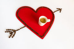 Cup of coffee on a red felt heart and arrow in diagonal Royalty Free Stock Photo