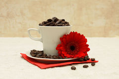 Cup of coffee and red flower. White cup, coffee beans and red flower on linen tablecloths Royalty Free Stock Image