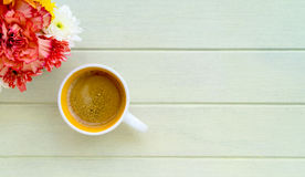 A cup of coffee and red flower on wooden table. With copy space Stock Image