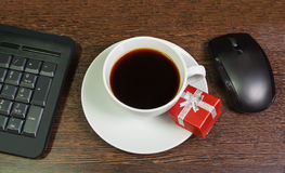 Cup of coffee, red gift box, mouse and keyboard Stock Photos