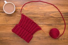 Coffee and red knitting on wooden background Royalty Free Stock Photography