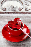 Cup of coffee and red lollipop in heart shape Stock Photography