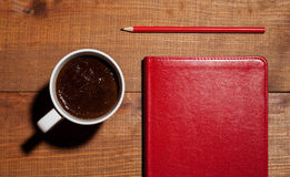 Cup of coffee, a red notebook and a red pencil Royalty Free Stock Photos