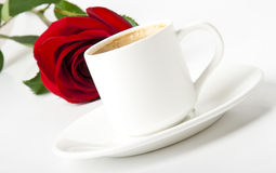 Cup of coffee and red rose. Cup of coffee and a red rose on white background Royalty Free Stock Photography
