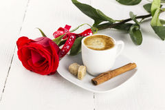 Cup of coffee, red rose, sugar and cinnamon on a white wooden ba. Ckground Stock Photos