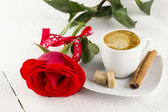 Cup of coffee, red rose, sugar and cinnamon on a white wooden ba. Ckground Royalty Free Stock Images