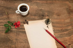 Cup of coffee with red rosebud and pen on white paper. Royalty Free Stock Photo