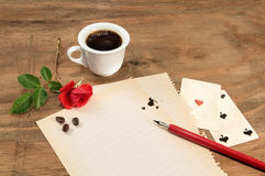 Cup of coffee with red rosebud and pen on white paper. Royalty Free Stock Image