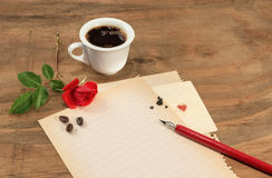 Cup of coffee with red rosebud and pen on white paper. Stock Photos