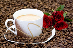 Cup of coffee and red roses Stock Photos