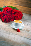 Cup of coffee and red roses Royalty Free Stock Photo