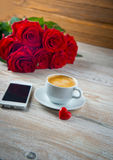 Cup of coffee and red roses Royalty Free Stock Image