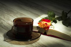 Cup of the coffee relating to the book with the rose Royalty Free Stock Photo