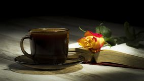 Cup of the coffee relating to the book with the rose Stock Photography
