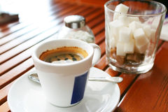 Cup of coffee on restaurant table. Near glass of sugar Stock Image