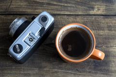 Cup of coffee with retro camera Royalty Free Stock Photo