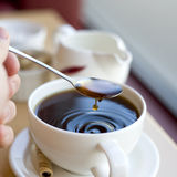 Cup of coffee with ripples. Cup of coffee with a spoon dripping and making ripples Stock Image