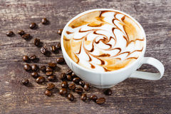 Cup of coffee and roasted bean on old wooden table Royalty Free Stock Photography
