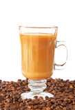 Cup of coffee and roasted beans. Cup of coffee with milk and roasted beans Stock Images