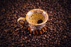 Cup of coffee on roasted coffee beans. Stock Photo