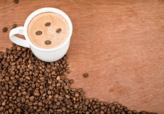 A cup of coffee and roasted coffee beans. On wooden background Royalty Free Stock Photos