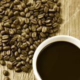 Cup of coffee and roasted coffee beans, in sepia toning Royalty Free Stock Images