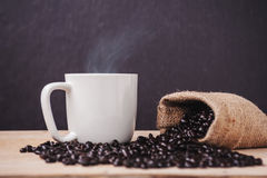 Cup of coffee with roasted coffee on a dark wooden and smoke. Still life tone stock image