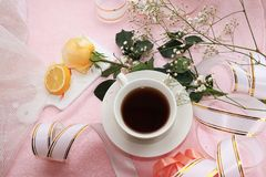 A cup of coffee and a rose on a pink background, a lemon and a festive ribbon. On the morning table, good morning wishes royalty free stock photo