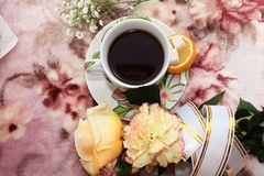 A cup of coffee and a rose on a pink background, a lemon and a festive ribbon. On the morning table, good morning wishes royalty free stock photography
