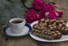 Cup of coffee, roses and plate with different cookies on a table Stock Photos