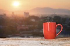 A cup of coffee on a rustic table against the morning rising sun stock photo