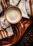 Cup of coffee on rustic wooden background with kitchen towel Royalty Free Stock Images