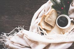 Cup of coffee on rustic wooden serving tray in the cozy bed with blanket. Knitting warm woolen sweater in the winter weekend, Royalty Free Stock Image