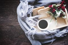 Cup of coffee on rustic wooden serving tray in the cozy winter with blanket. Knitting warm woolen sweater in the winter weekend, t Royalty Free Stock Photo