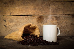 Cup of coffee sacks of coffee beans on the old wooden floor. Royalty Free Stock Photos