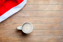 Cup of coffee and santa claus hat on the wonderful brown wooden Royalty Free Stock Images