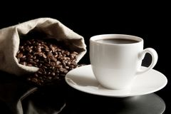 Cup of coffee with saucer with bag with coffee beans on black Royalty Free Stock Photo