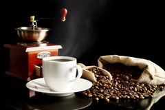 Cup of coffee with saucer,bag,coffee beans on black Stock Image