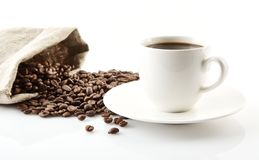 Cup of coffee with saucer with bag with coffee beans on white Royalty Free Stock Images