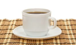 Cup of coffee and saucer on a bamboo napkin Stock Images