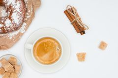 Cup of coffee with saucer and brown sugar, pastry and cinnamon sticks tied with rope isolated on white Stock Image