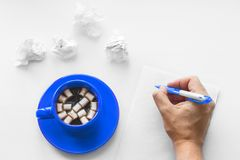 Cup of coffee on saucer with marshmallows, hand with pen writing on a blank sheet of paper and crumpled sheets of paper. Stock Photo